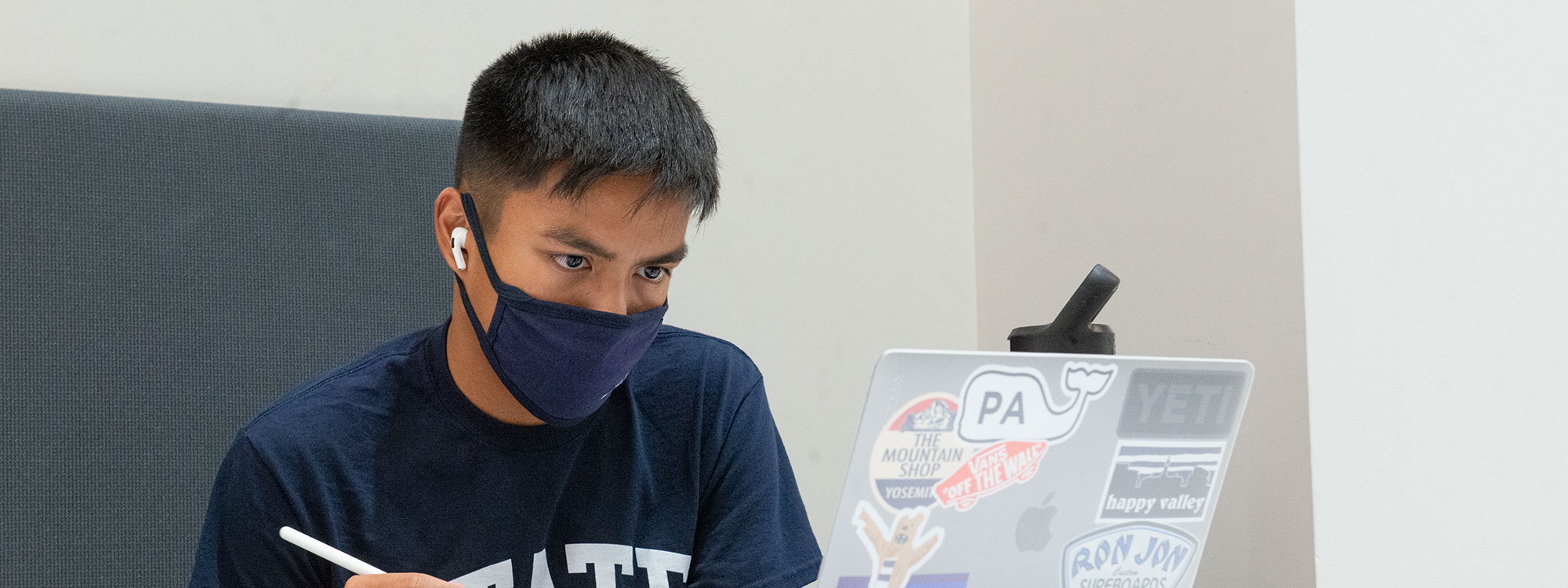 Photo of student wearing a mask working on a laptop